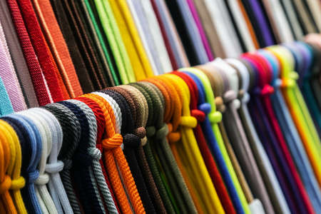different colors of shoelaces or rope on the shelves of a clothing factory or production Foto de archivo