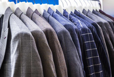 mens jackets in check and stripes hang on hangers in the atelier Foto de archivo