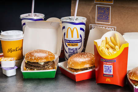 various burgers with French fries, cola and sauces from McDonalds restaurant.