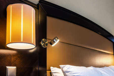 floor lamp on the wall above the bed in the room Foto de archivo
