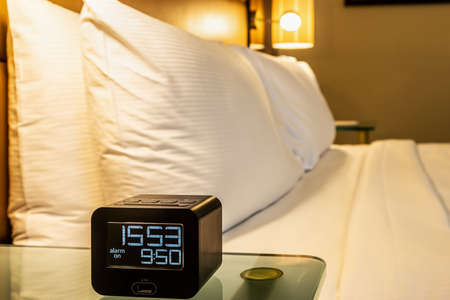 the alarm clock is placed on the bedside table at home Foto de archivo