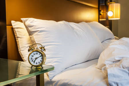 mechanical alarm clock is placed on the bedside table at home