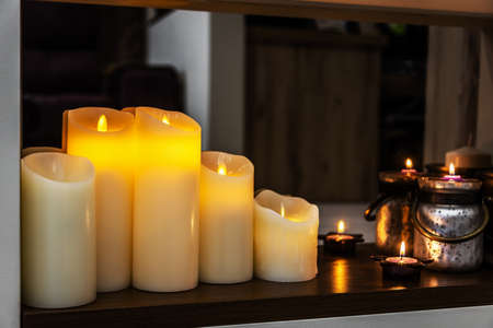 led electric and wax candles stand in the home fireplace
