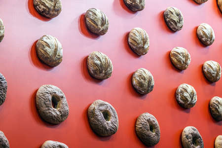 loaves of bread hang on the red wall Foto de archivo