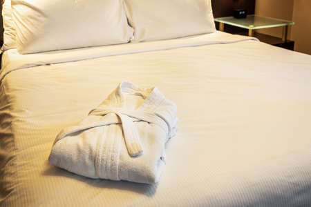 the bathrobes are folded on the bed in the hotel room
