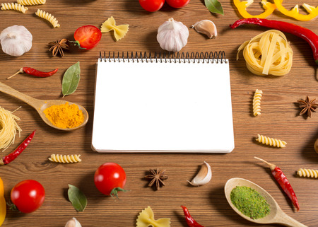 Notebook for recipes, vegetables and spices on wooden table photo