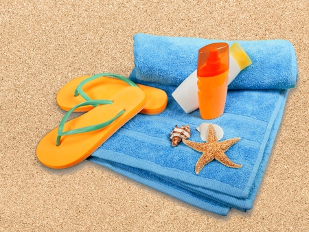 flipflop: Suntan Lotion, Flip-flop, Towel. Stock Photo