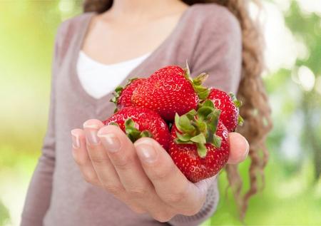 holding aloft: Organic, Strawberry, Women. Stock Photo
