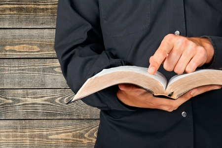 man holding book: Bible, Priest, Preacher.