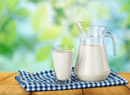 milk jug: Milk, glass, tablecloth.
