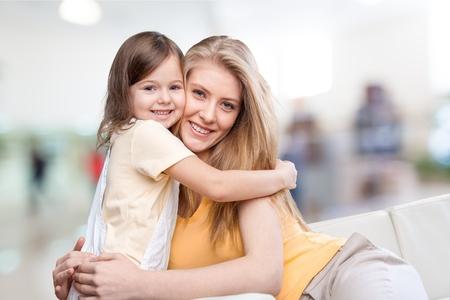 family at home: Mom, hugging, sofa.