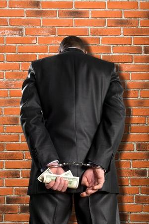 criminal activity: Handcuffs, Currency, Bribing.