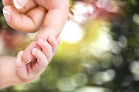 Baby, lidská ruka, matka. Reklamní fotografie