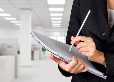 note pad: Businesswoman holding pencil and note pad