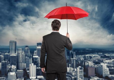 El hombre de negocios que sostiene el paraguas rojo Foto de archivo - 43854648