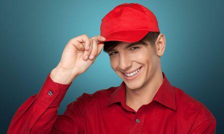 birretes: hombre joven con el casquillo rojo y una camisa Foto de archivo