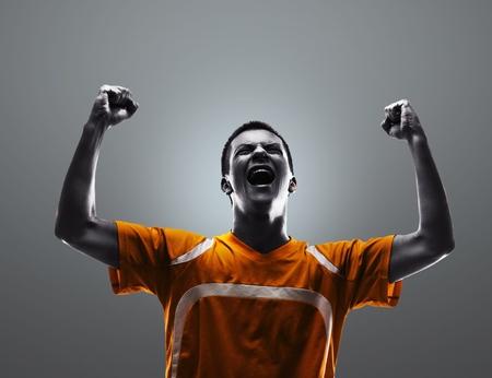 futbolista: Emocionado jugador de fútbol de sexo masculino
