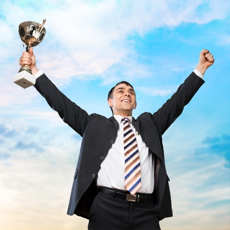 winning: Happy businessman holding trophy with arms raised