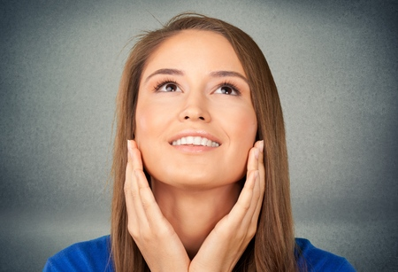young woman face: Young woman looking up with hands on her face Stock Photo