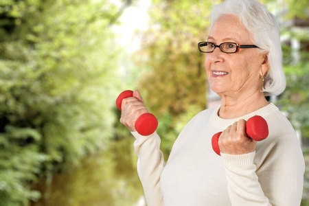 80 plus adult: Senior woman working out with dumbbells Stock Photo