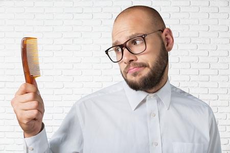 peine: Hombre calvo que sostiene un peine