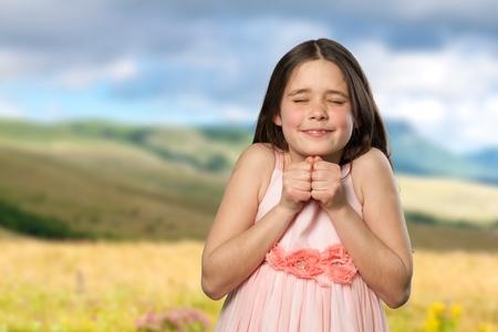 puños cerrados: niña emocionada con los ojos cerrados