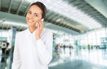 working attire: Women with working attire smiling while talking to the phone.