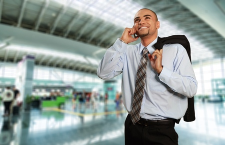 working attire: Men with working attire smiling while talking to the phone.