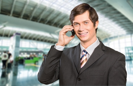 working attire: Businessman with working attire smiling while talking to the phone.