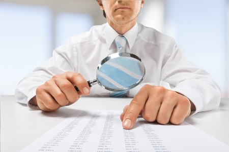 Man holding a Magnifying Glass. Stock Photo