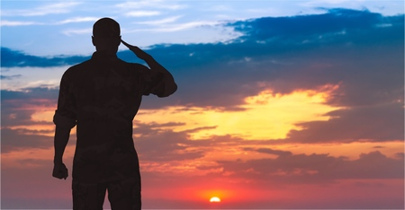 Silhouette of a soldier saluting during sunset. Stock Photo