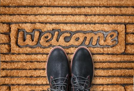Shoes on new welcome doormat on wooden floor