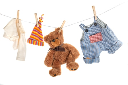 Teddy bear hanging on clothesline with clothes Banco de Imagens