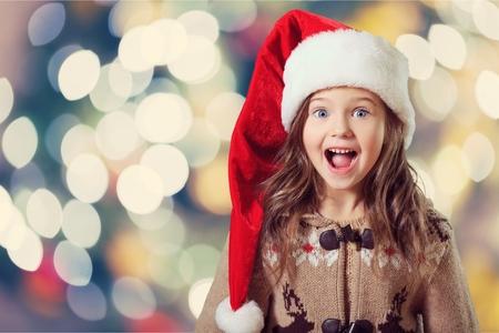 Gelukkig kindmeisje in een Kerstmishoed. Stockfoto