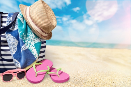 swimming shoes: Beach bag on sea background.