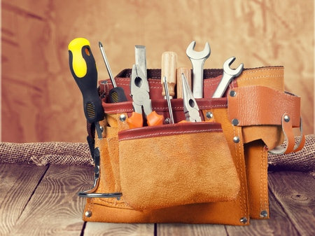 Tool belt with tools on wooden background Stock Photo