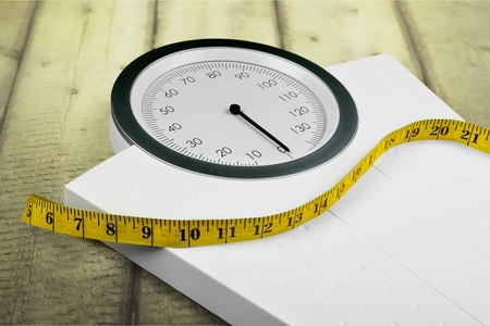 Bathroom scale with a measuring tape, close-up view