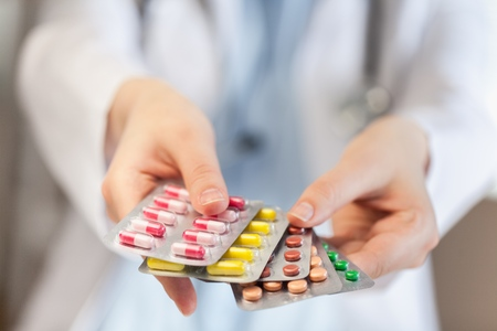 Doctor hand holding pill.