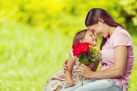 Woman and child with bouquet of flowers.