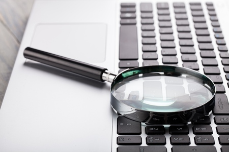 Laptop computer with magnifying glass. Stockfoto