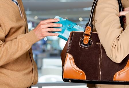 男性の手が女性のバッグから財布を盗んだ