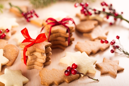 Tasty Christmas cookies with red ribbon on background