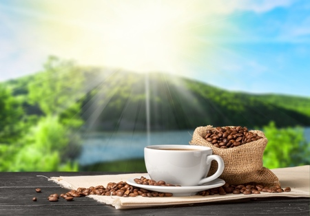 Hot Coffee cup with Coffee beans on the wooden table and the plantations background Stock Photo