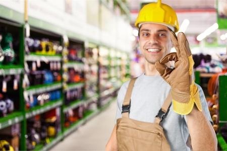 Ouvrier faisant un geste parfait avec sa main gantée en se concentrant sur sa main sur un fond gris avec un point culminant et un fond. Banque d'images - 89590807