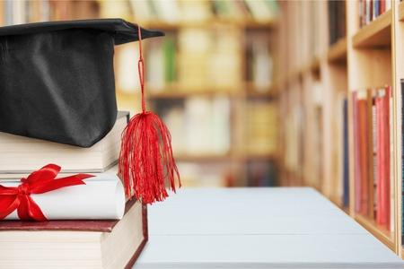Un birrete de graduación en la parte superior de una pila de libros, con rollo de pergamino atado en cinta roja. Foto de archivo