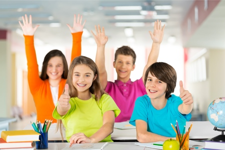 four School kids raise hands up and giving thumbs up Stock Photo