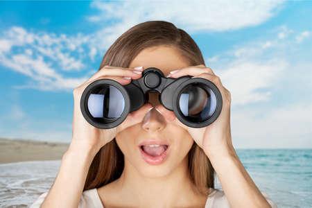 Young lady trying binoculars. photo