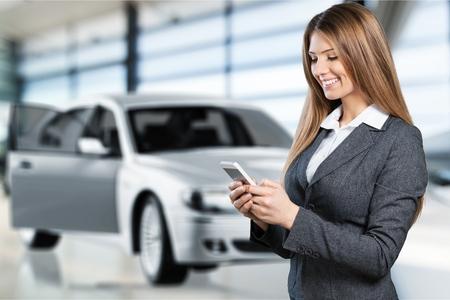 Woman using phone on car background. Stock fotó