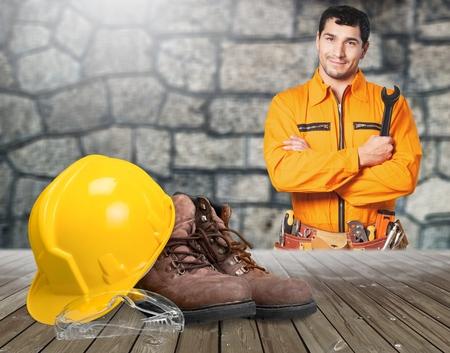 Schutzausrüstung für die Bauindustrie. Gelber Helm oder Schutzhelm, schwarze Stiefel und Schutzbrille aus Kunststoff.