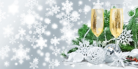 Champagne glasses with Christmas decorations on background
